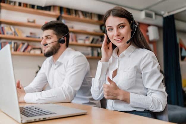 Mujer trabaja en call center con auriculares como despachador respondiendo llamadas telefónicas de clientes Foto Premium
