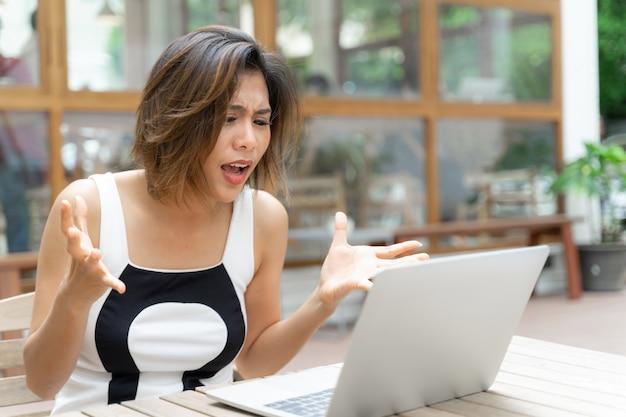 Mujer trabajadora que se siente molesta con la computadora portátil Foto gratis