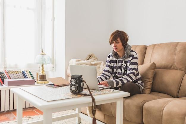 Mujer trabajando con el ordenador en el salón de su casa ...