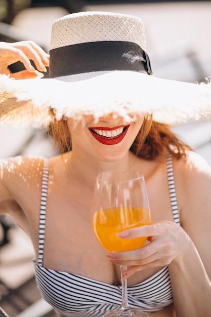 Mujer en traje de baño en vacaciones bebiendo jugo Foto gratis