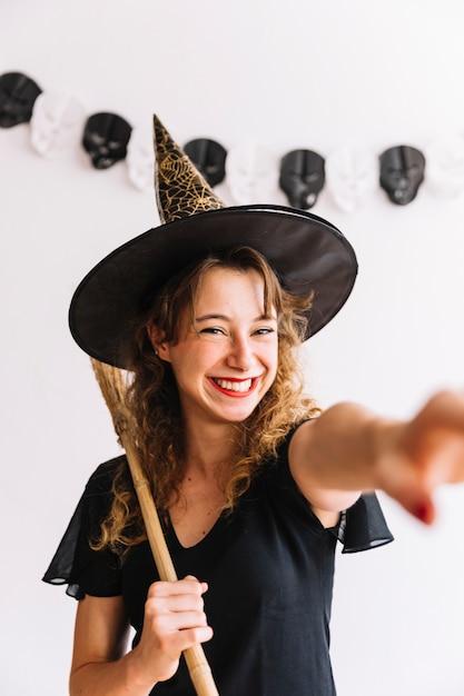 Mujer en traje de bruja con escoba negra Foto gratis