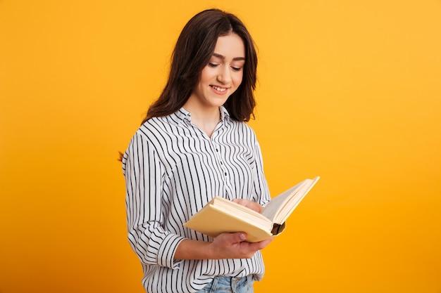 Mujer triguena sonriente en libro de lectura de la camisa Foto gratis