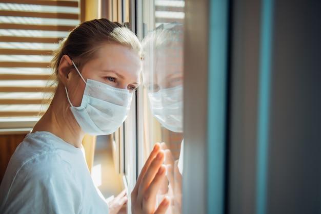 La mujer triste en una máscara médica protectora mira por la ventana, de cerca. aislamiento, cuarentena, quedarse en casa. protector contra covid-19 Foto Premium