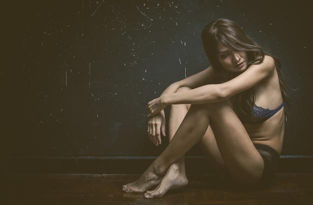 Mujer triste sentada sola en una habitación vacía. Foto gratis