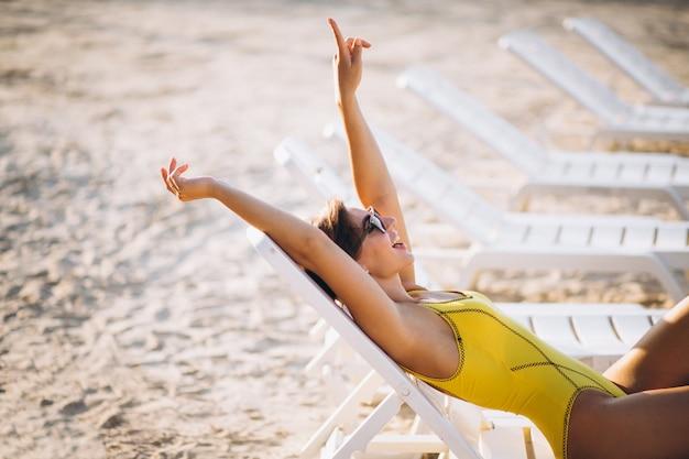 Mujer tumbada en la cama de la piscina junto al mar Foto gratis