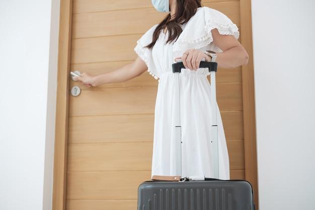 Mujer turista feliz con mascarilla quirúrgica y puerta de apertura Foto Premium