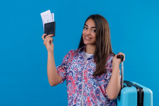 Mujer turista sosteniendo maleta de viaje y pasaporte con boletos con una sonrisa en la cara feliz y positiva Foto gratis