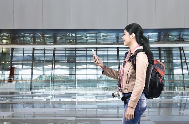 Mujer turística asiática sonriente con la mochila usando el teléfono móvil Foto Premium