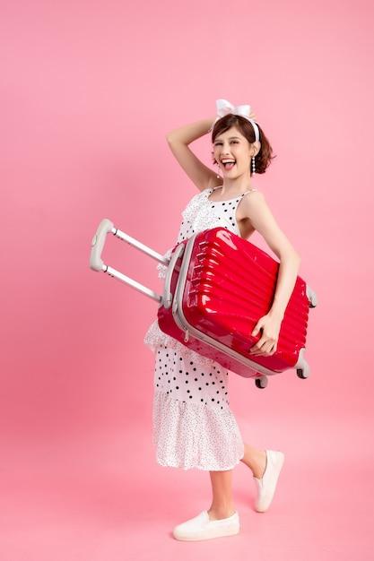 Mujer turística del viajero en ropa casual del verano con la maleta del viaje aislada en rosa Foto gratis