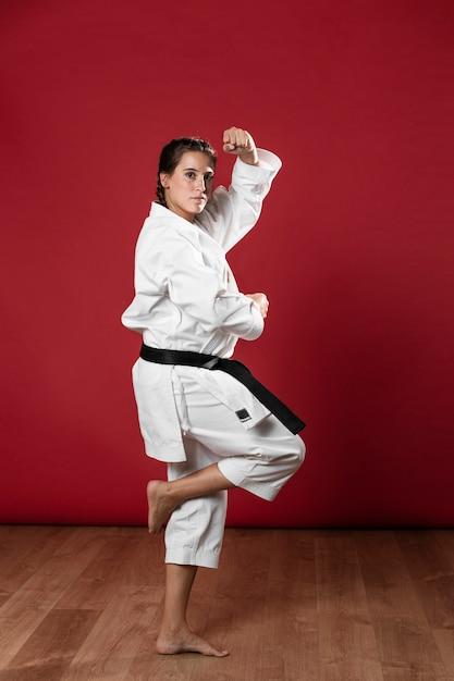 Mujer en uniforme de artes marciales ejercicio de karate Foto gratis