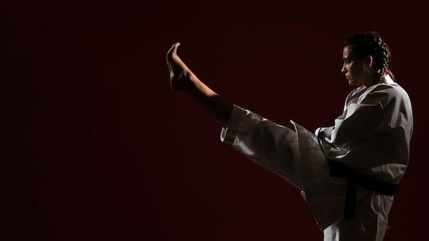 Mujer en uniforme de karate blanco y copia espacio de fondo Foto Premium
