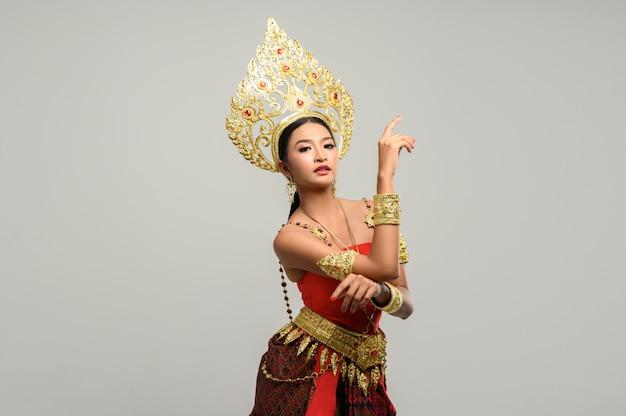 La mujer usa ropa tailandesa. la mano derecha se coloca sobre la mano izquierda. Foto gratis