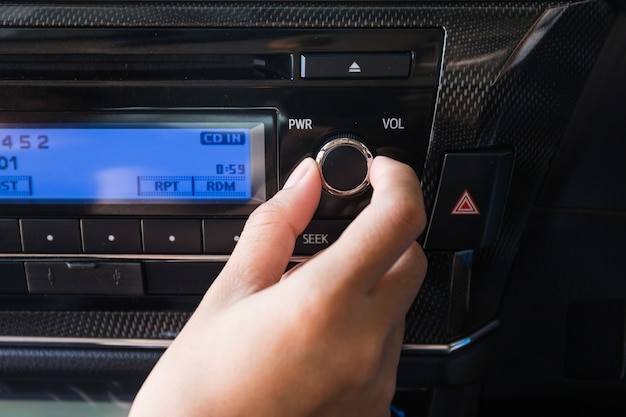 Mujer usando control de volumen de audio de coche. Foto Premium