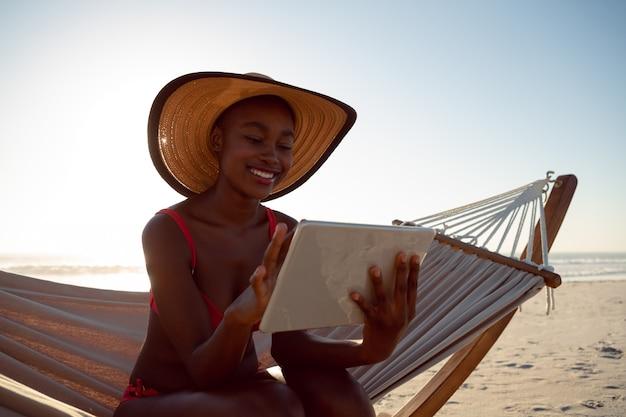 Mujer usando tableta digital mientras se relaja en una hamaca en la playa Foto gratis
