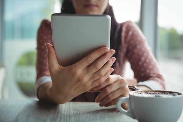 Mujer usando tableta digital mientras toma una taza de café Foto gratis