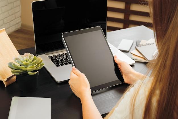 Mujer usando tableta digital sentado en una mesa en una oficina Foto Premium