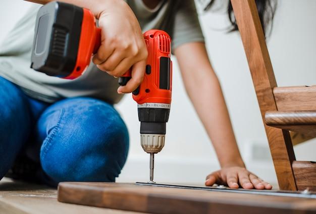 Mujer utilizando taladro de mano para montar una mesa de madera Foto gratis