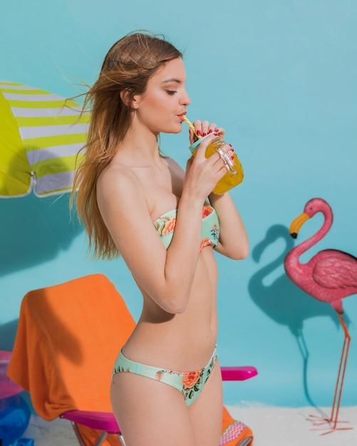 Mujer de verano tomando jugo de naranja Foto gratis