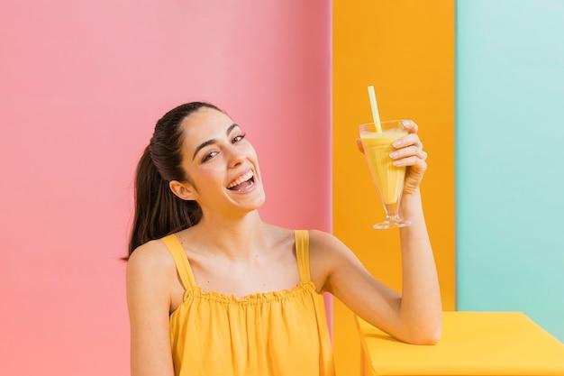 Mujer vestida de amarillo con un vaso de jugo Foto gratis