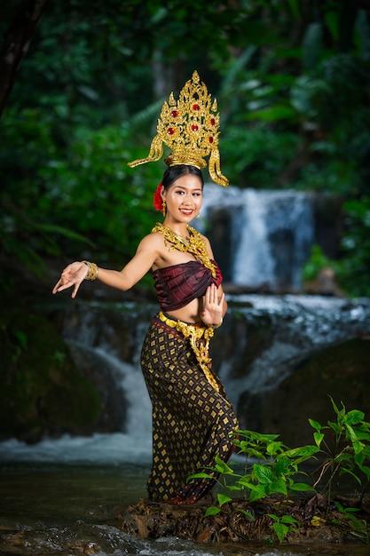 Una mujer vestida con un antiguo vestido tailandés en la cascada. Foto gratis