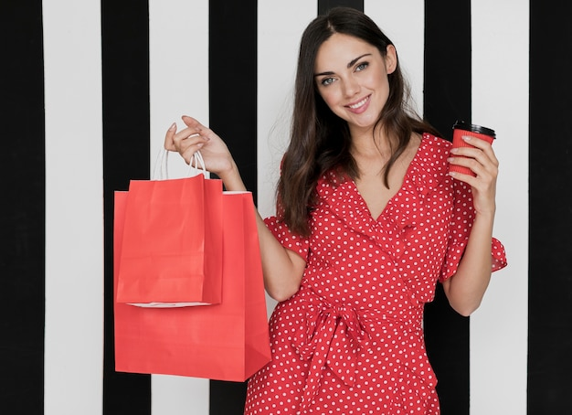 Mujer vestida con café y bolsas de compras sonriendo a la cámara Foto gratis