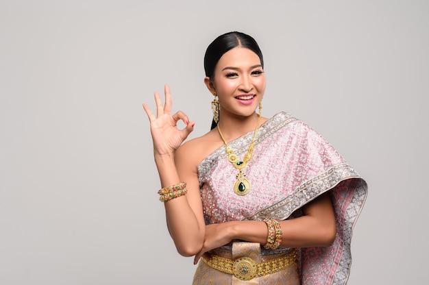 Mujer vestida con ropa tailandesa y mano que simboliza ok Foto gratis