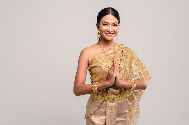 Mujer vestida con ropa tailandesa que respeta Foto gratis