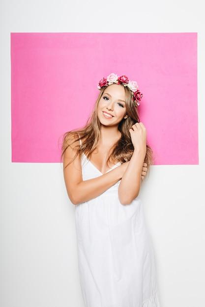 Mujer en vestido de algodón blanco con flores en el pelo sonriendo Foto gratis