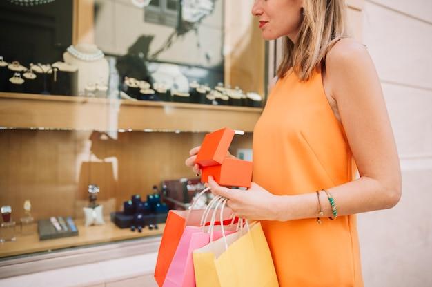 Mujer en vestido amarillo enfrente de tienda de joyería Foto gratis