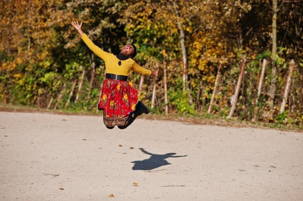 Mujer en vestido amarillo y rojo en el parque otoño otoño dorado Foto Premium
