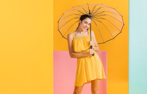 Mujer en vestido amarillo con sombrilla Foto gratis