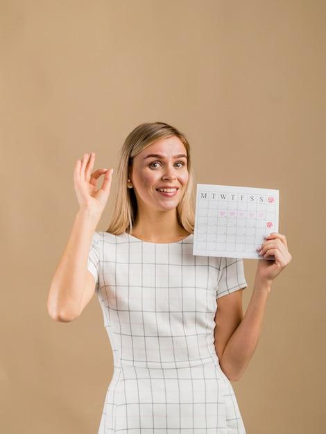Mujer con un vestido blanco que muestra su calendario de época Foto gratis