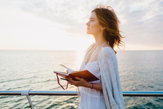 Mujer en vestido blanco de verano caminando por el mar al amanecer con el libro diario en el estado de ánimo romántico pensando y tomando notas Foto gratis