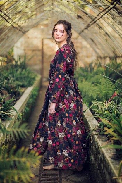 Mujer con vestido floral y pies descalzos Foto gratis