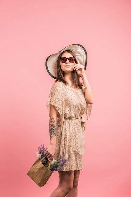 Mujer en vestido con flores en bolsa Foto gratis