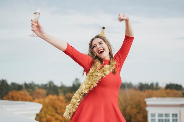 Mujer en vestido rojo bailando en la azotea Foto gratis
