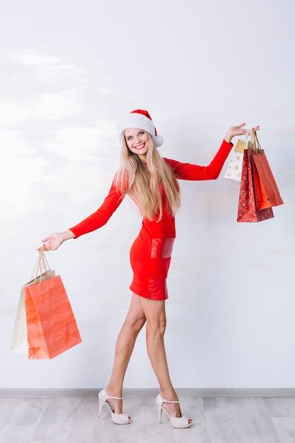 e42af83b Mujer en vestido rojo con bolsas de compras en las manos | Descargar ...