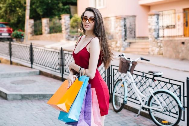 Mujer en vestido rojo sosteniendo bolsas de papel Foto gratis