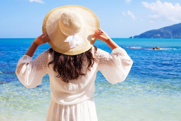 Mujer en vestido de verano con sombrero de paja Foto Premium