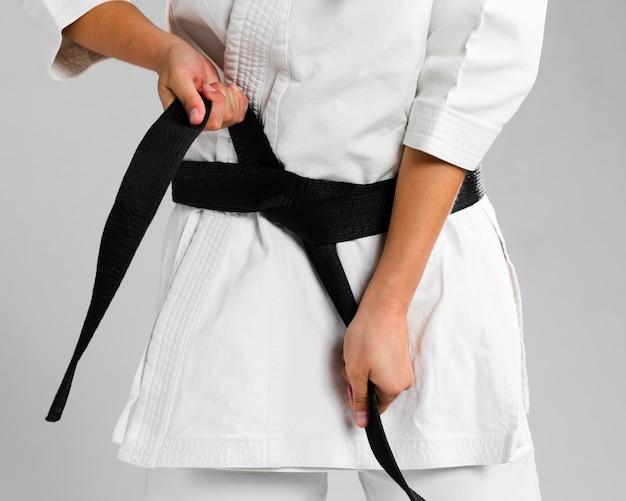 Mujer vestirse de uniforme y ponerse el cinturón Foto gratis