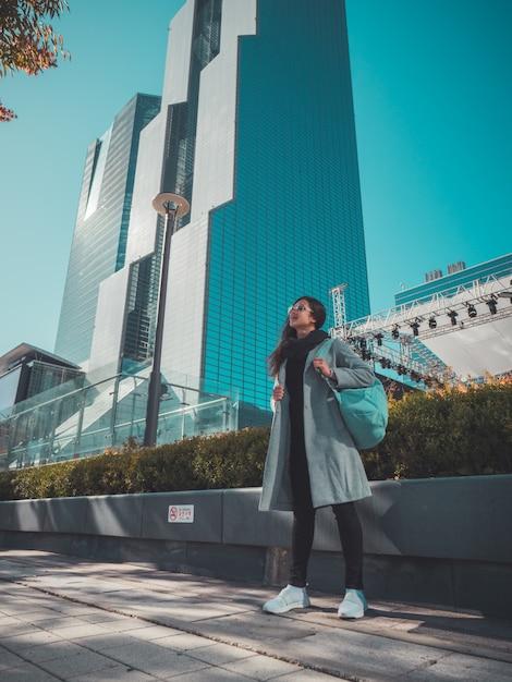 Mujer viajera en seúl cerca de rascacielos. vista de otoño Foto Premium