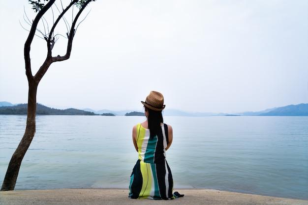 La mujer del viajero disfruta mirando el hermoso lago con montañas en el fondo Foto Premium