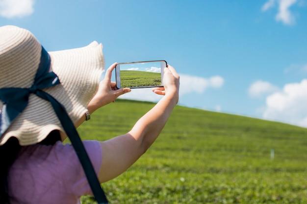 La mujer del viajero que sostiene el teléfono y toma la foto en el paisaje archivado verde Foto Premium