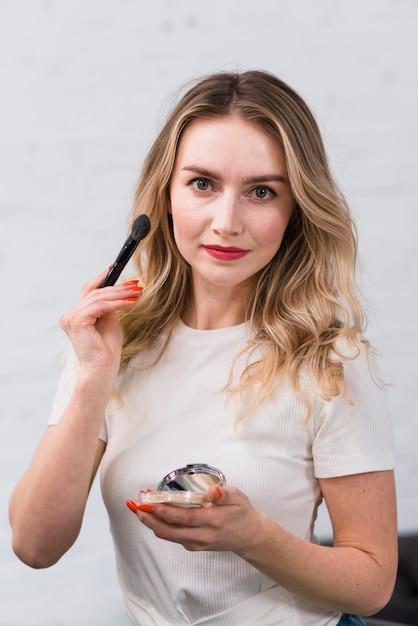 Mujer visagiste posando para cámara con cosméticos. Foto gratis