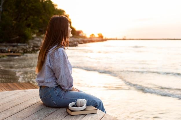 Mujer de vista lateral mirando el mar al atardecer Foto gratis