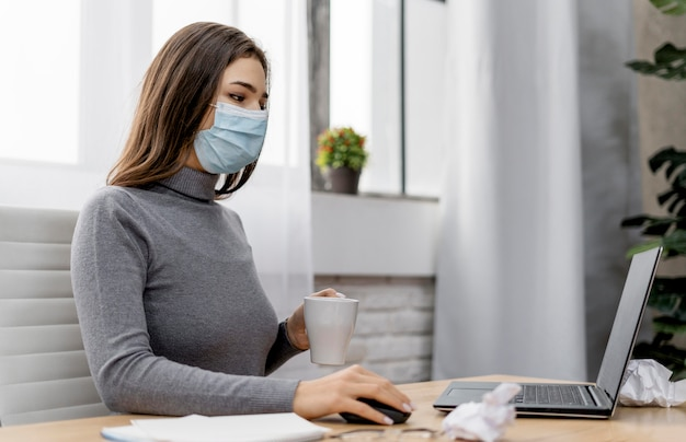 Mujer vistiendo una máscara médica mientras trabaja desde casa Foto gratis