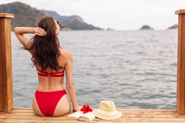 Mujer vistiendo traje de baño de pie en el muelle Foto gratis