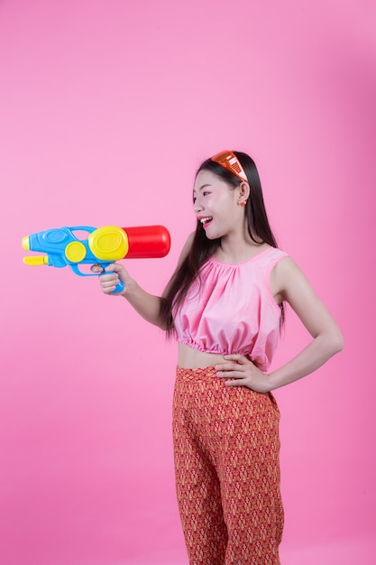 Una mujer se vistió en una ropa popular tailandesa tradicional que sostenía un arma de agua en un fondo rosado. Foto gratis