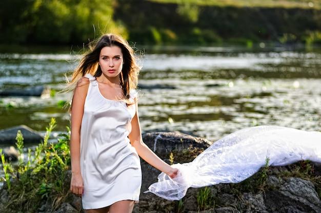 Mujer yang posando en el río al atardecer. Foto Premium