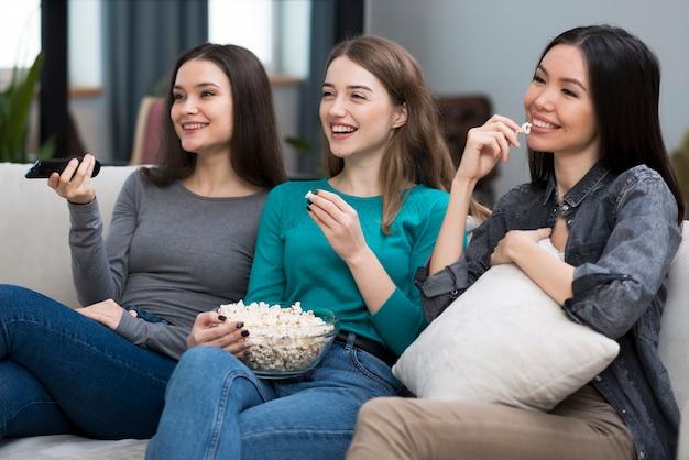 Mujeres adultas positivas viendo series juntas Foto gratis
